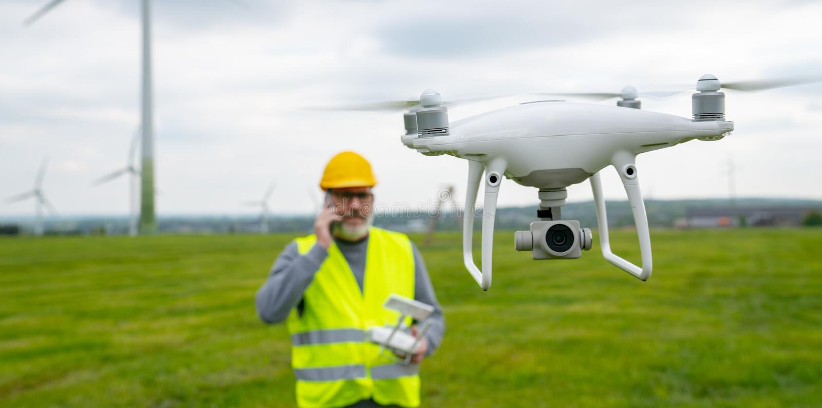 Drone operated by construction worker inspecting wind turbine royalty free stock image