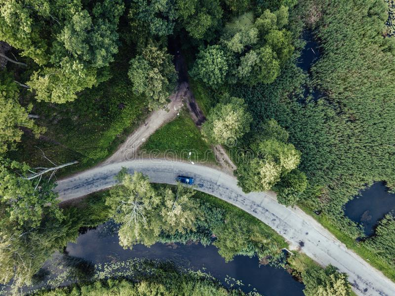 Drone Photo of Car Driving on the Road by the River under the Trees, Top Down View in Early Spring on Sunny Day - Concept of royalty free stock photos