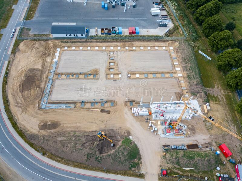 Drone photo of a large construction site on which a factory building is being erected. The foundations for the piers have been stock images