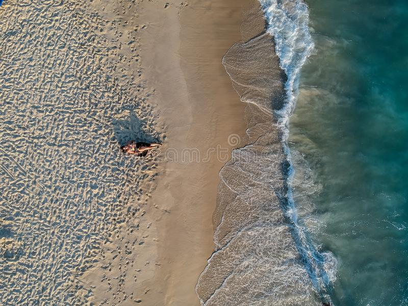 Drone photo of woman lying on the beach during sunset royalty free stock photography