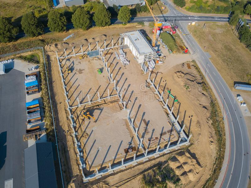 Drone photograph of a construction site with concrete supports for a factory building. A drone photograph of a construction site with concrete supports for a stock photo
