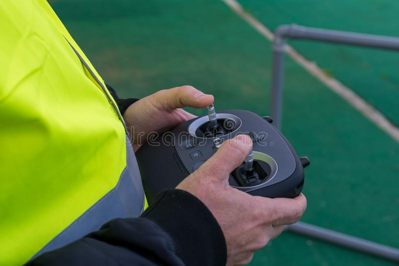 Drone pilot during an exercise wearing a yellow jacket. Pilot pilot aircraft remotely during a simulation. stock photo