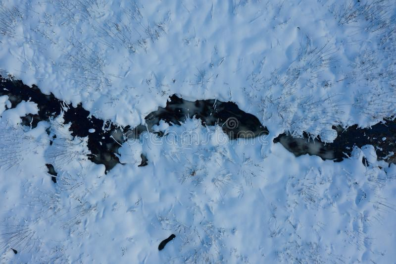 Drone point of view of frozen river among snow. Aerial winter landscape. Aerial winter. Aerial Snow texture. Beautiful snowy royalty free stock photography