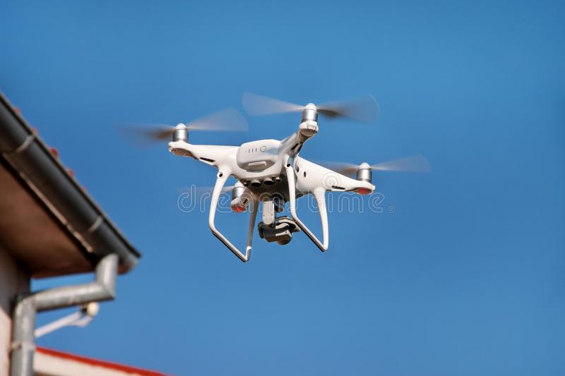 Drone quad copter fly on blue sky in background. Modern drone is flying in air, to take photos and record footage from above. Drone with four propellers stock photo