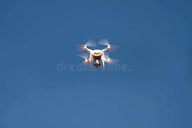 Drone quad copter fly on blue sky in background. Modern drone is flying in air, to take photos and record footage from above. royalty free stock photos