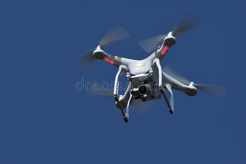 Drone quad copter flying and hovering in the blue sky. Drone quad copter with digital camera flying and hovering in the blue sky royalty free stock photography