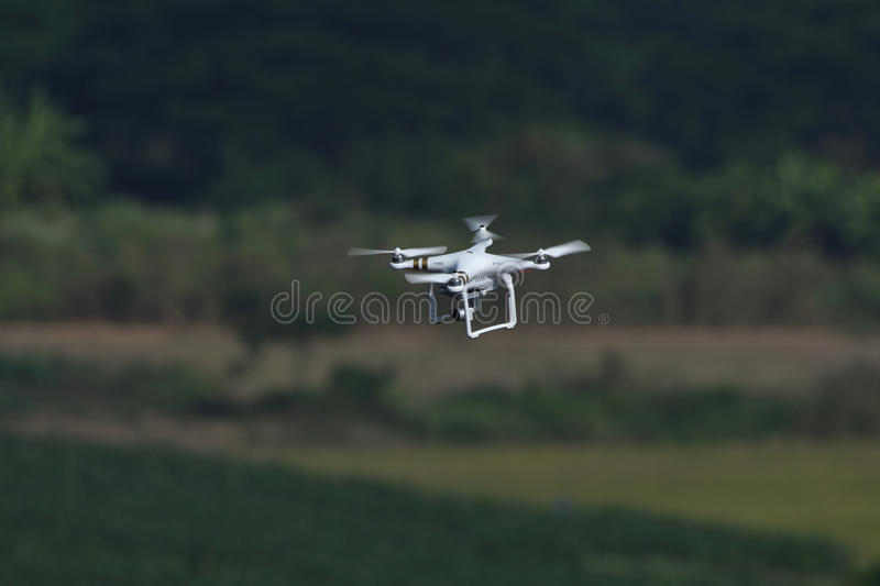 Drone quad copter flying and hovering in landscape background. Drone quad copter with digital camera flying and hovering in landscape background royalty free stock photography