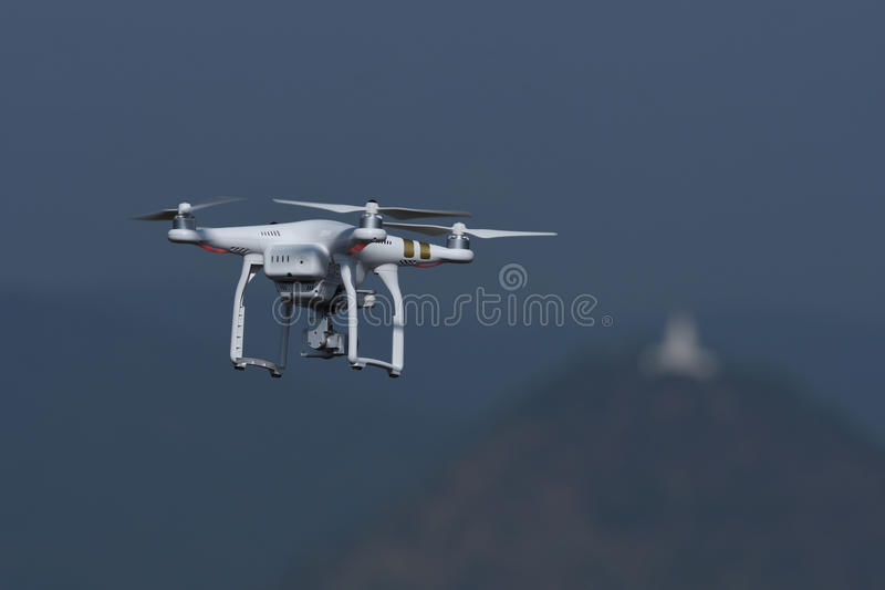 Drone quad copter flying and hovering in landscape background. Drone quad copter with digital camera flying and hovering in landscape background royalty free stock photo