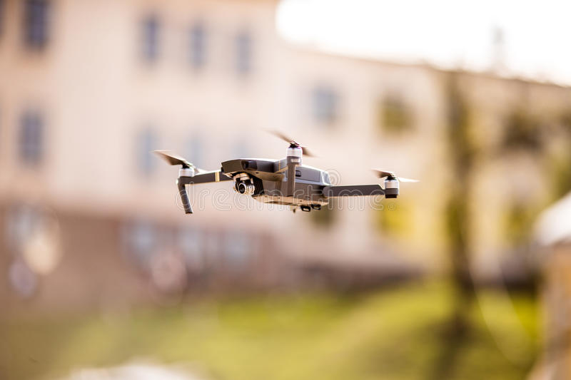 Drone quad copter with high resolution digital camera flying hovering in the blue sky over the city. Drone quad copter with high resolution digital camera flying royalty free stock photo