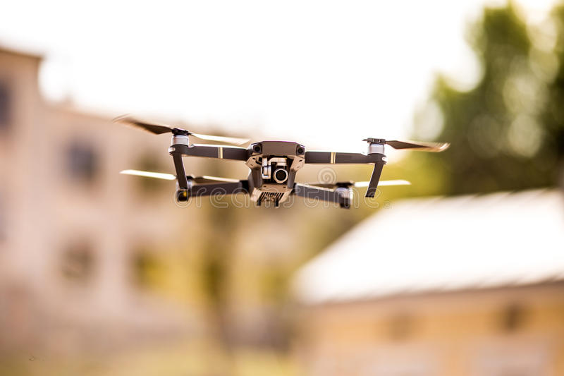 Drone quad copter with high resolution digital camera flying hovering in the blue sky over the city. Drone quad copter with high resolution digital camera flying royalty free stock photography