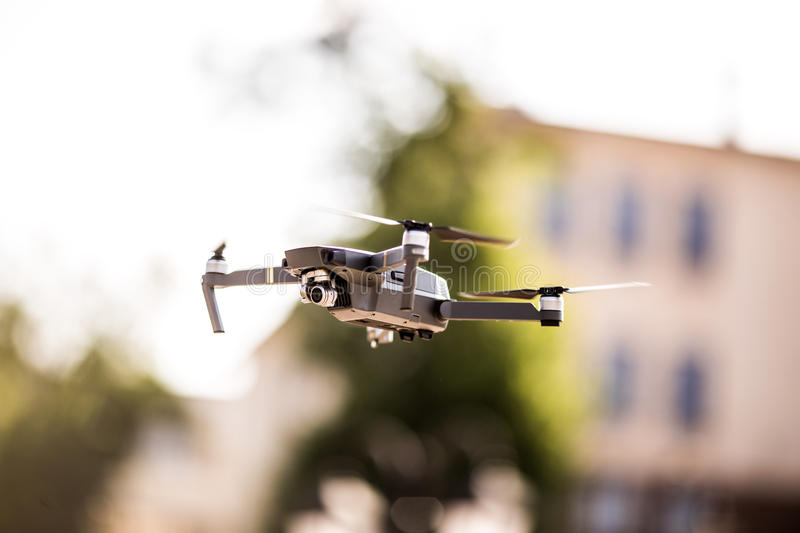 Drone quad copter with high resolution digital camera flying hovering in the blue sky over the city. Drone quad copter with high resolution digital camera flying stock images