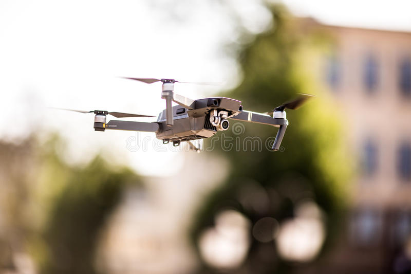 Drone quad copter with high resolution digital camera flying hovering in the blue sky over the city. Drone quad copter with high resolution digital camera flying stock photography