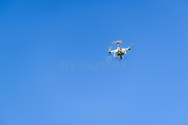 Drone quad copter flying in the blue sky. Drone quad copter with onboard high resolution digital camera flying in the blue sky royalty free stock image