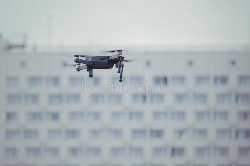 Drone quad copter with onboard high resolution digital camera flying over the city skyscrapers in the sky. stock image