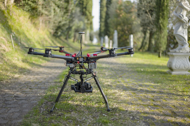 Drone Quadcopter in the Alley. Horizontal shot of unmanned quadcopter standing in the brick alley surrounded by ancient statues and vivid greenery stock images