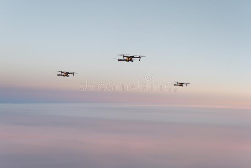 Drone quadcopter with digital camera above sunset sky and Earth Surface. Concept royalty free stock images