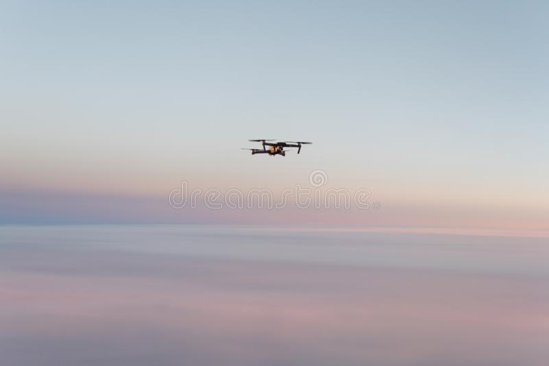 Drone quadcopter with digital camera above sunset sky and Earth Surface. Concept stock photos