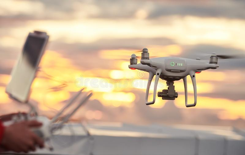 Drone quadcopter with digital camera flying at sunset stock photos