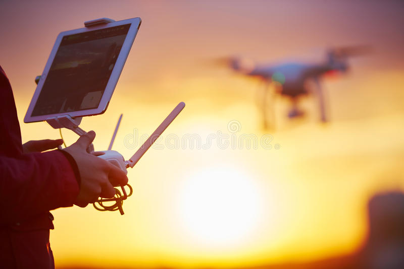 Drone quadcopter flying at sunset. Drone quadcopter flying or hovering by under remote control operation in sunset. Very shallow field of view royalty free stock image