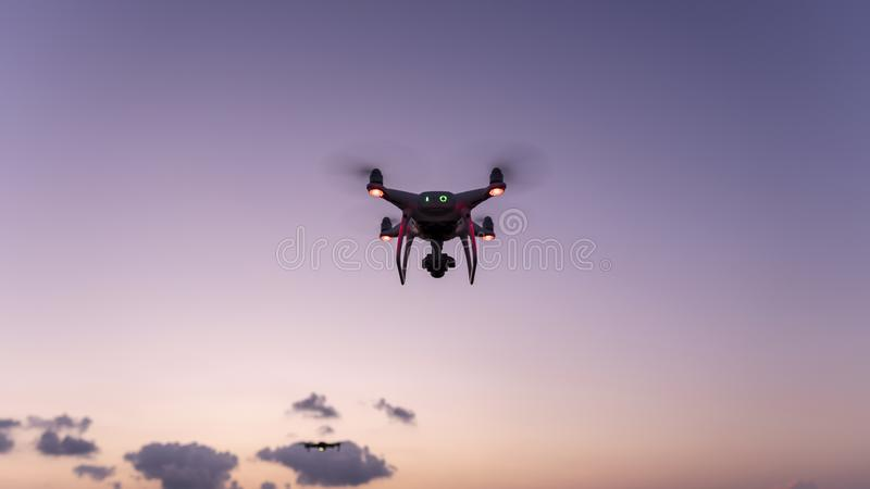Drone quadcopters with high resolution digital camera Drone flying in sunset or sunrise beautiful sky stock photography