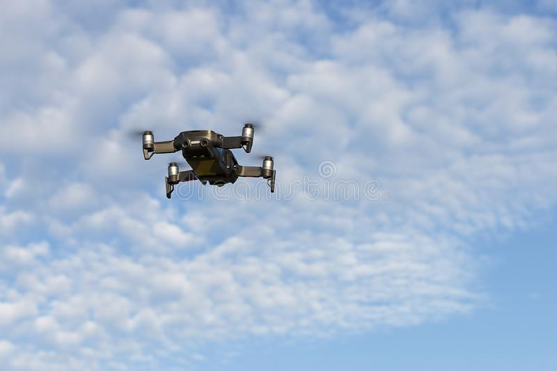 A drone, a quadrocopter with a camera for video shooting, flies against a blue sky with clouds stock photo