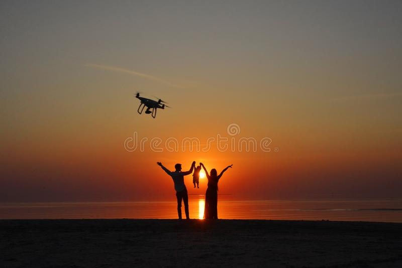 Drone quadrocopter. Dark silhouette family photo at sunset, beach, sea stock image