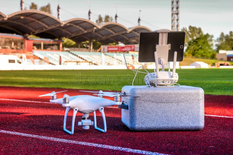 Drone is ready for take off. White quadcopter with four motors and propellers standing in large stadium. Next to its carry box and remote controller with royalty free stock image