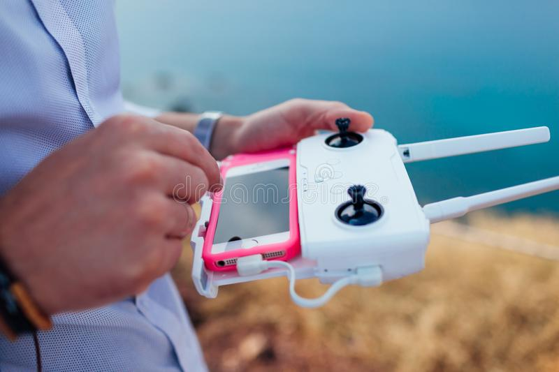 Drone remote control. Man holding copter controller with smartphone. Aerial video shooting. Drone remote control. Man holding copter controller with smartphone royalty free stock images