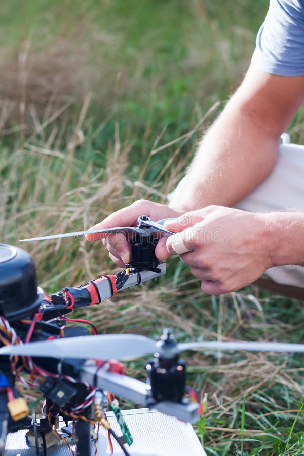 Drone repairing on the field. Person repairing a drone on the field royalty free stock photos