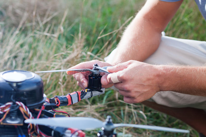 Drone repairing on the field. Person repairing a drone on the field stock photography