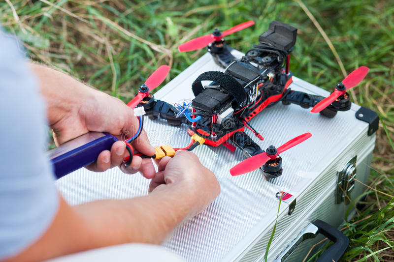 Drone repairing on the field. Person repairing a drone on the field royalty free stock images
