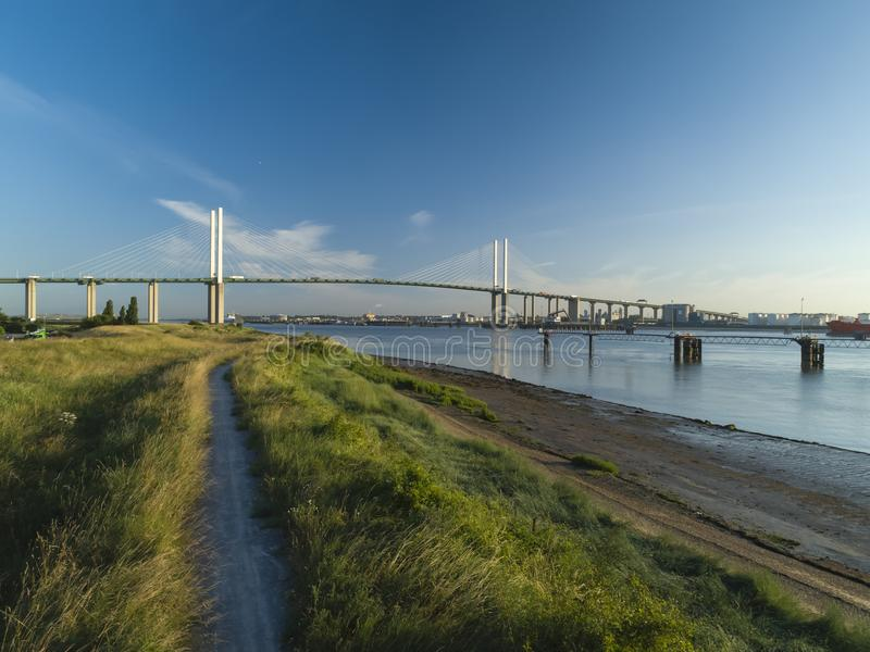 Drone shot above over grass on Thames riverbank with QEII bridge. Drone shot above over grass on Thames riverbank. Queen Elizabeth II bridge is in background royalty free stock photography