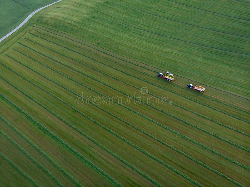 Drone shot of agricultural field with tractors harvesting hay. Aerial view of agricultural green field and tractors harvesting hay royalty free stock images