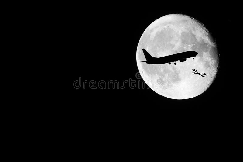 Drone Silhouette. A night shot of a drone against the almost full moon. Showing the dangers of drones against other passenger occupied aviation stock photos