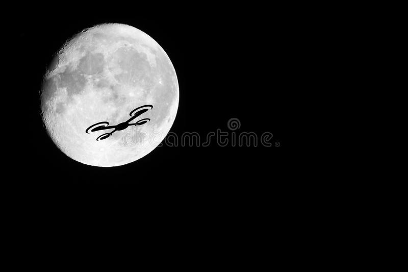 Drone Silhouette. A night shot of a drone against the almost full moon. Showing the dangers of drones against other passenger occupied aviation royalty free stock photo