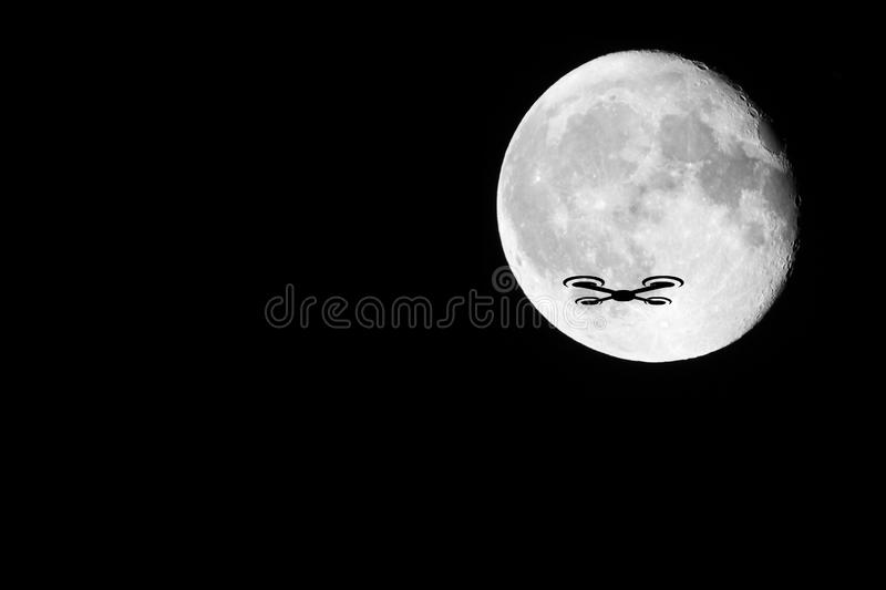 Drone Silhouette. A night shot of a drone against the almost full moon. Showing the dangers of drones against other passenger occupied aviation royalty free stock photos