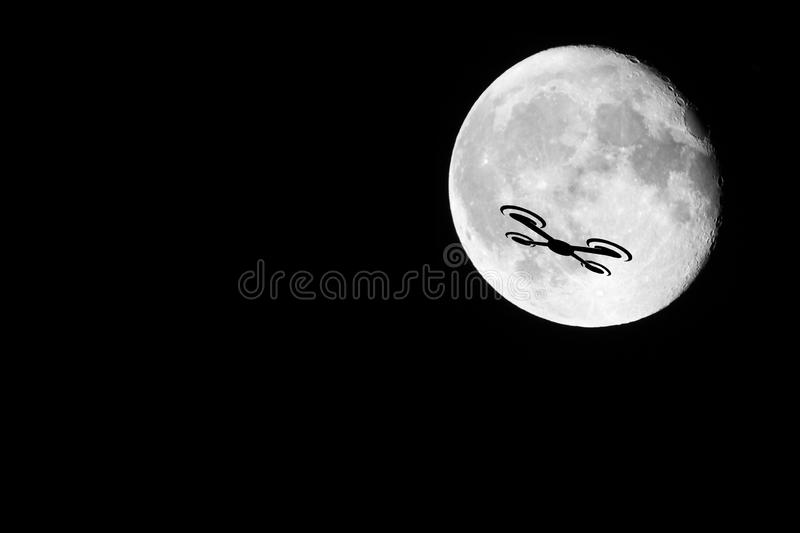Drone Silhouette. A night shot of a drone against the almost full moon. Showing the dangers of drones against other passenger occupied aviation royalty free stock images