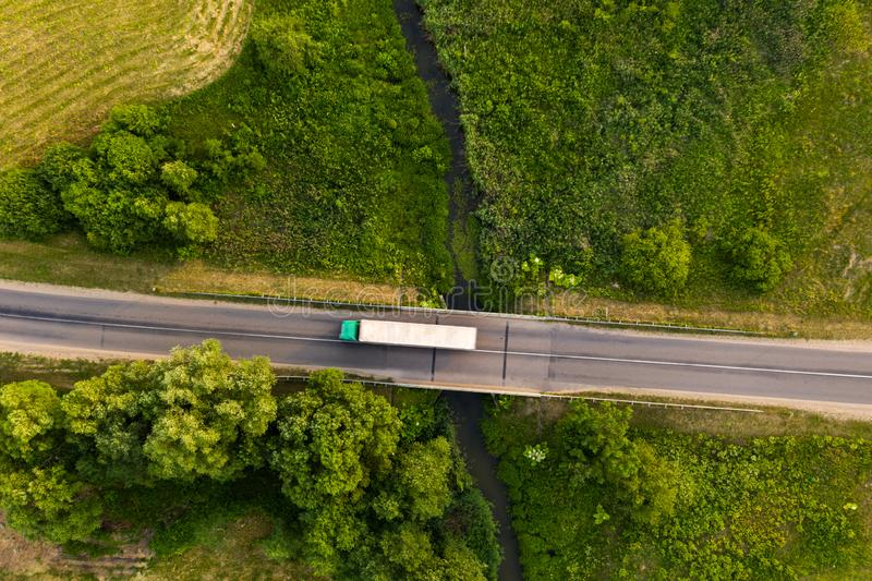 Drone top down view of truck driving remote road over small river stock image