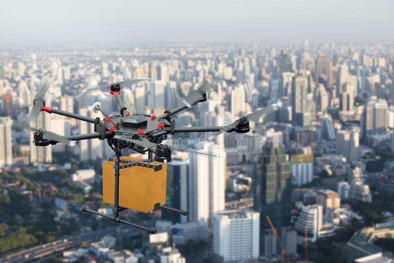 Drone transport flying with cardboard box above city stock image