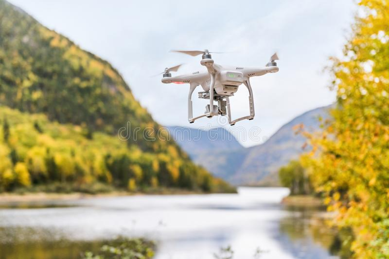 Drone uav flying in the air taking video of autumn forest foliage nature landscape in outdoors during fall season. Quad copter royalty free stock photo