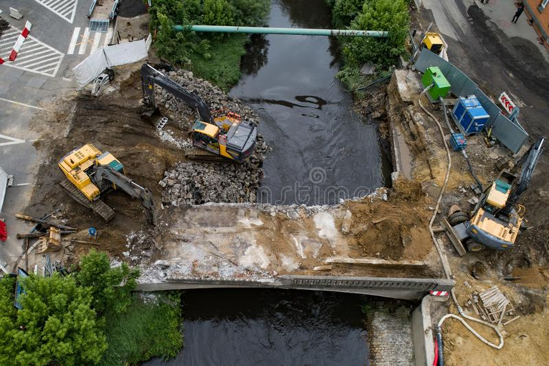 Drone view on excavators demolishing a road bridge. Heavy machinery stock photography