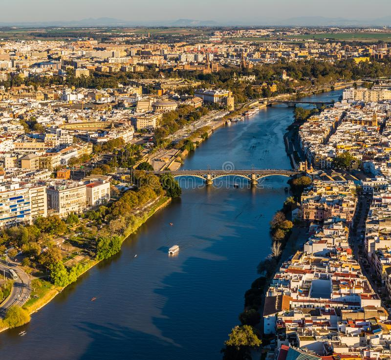 Drone view of old downtown Sevilla at sunset. Aerial view of old downtown Sevilla at sunset showing Guadalquivir river, Puente de Triana, Plaza de Toros, Plaza stock photo