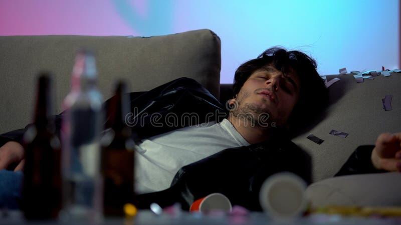 Dronk man slaapt op sofa na feestje thuis, lege flessen op tafel, verslaafd stock afbeeldingen