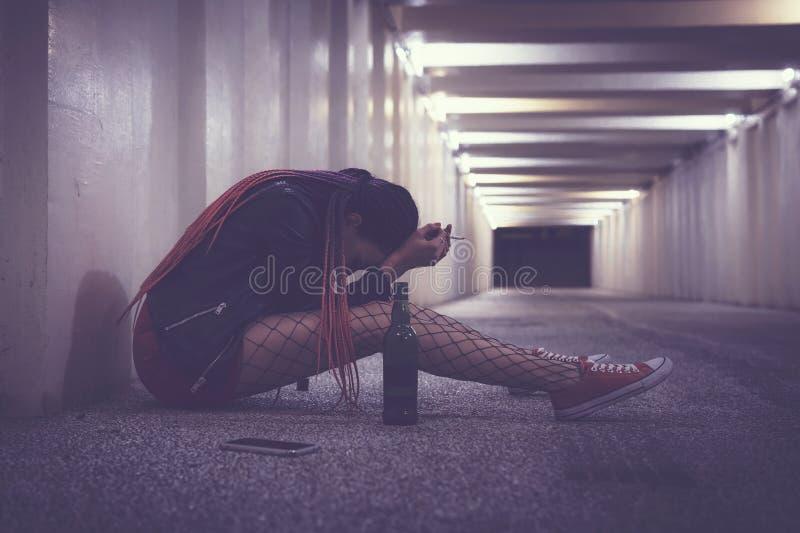 Dronken gedeprimeerde dakloze vrouw die in de onderdoorgang schreeuwen Tijdens de nacht stock foto's