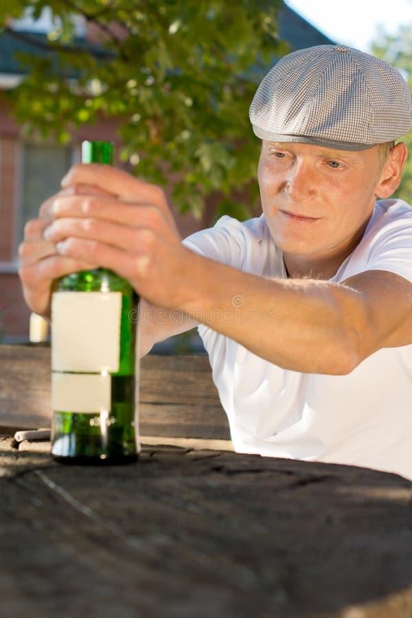Dronken gedeprimeerde mens die een fles wijn houden royalty-vrije stock foto