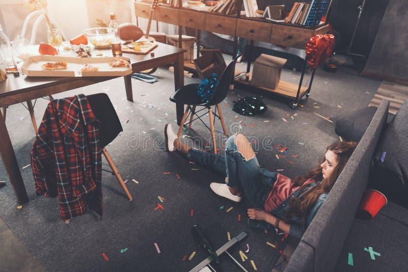 Dronken jonge vrouw die op vloer in slordige ruimte na partij liggen royalty-vrije stock foto's