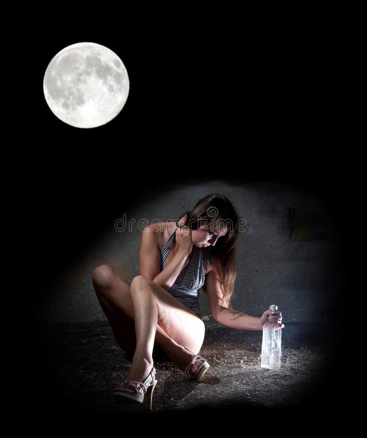 Dronken meisje met wodka in maanlicht stock foto's