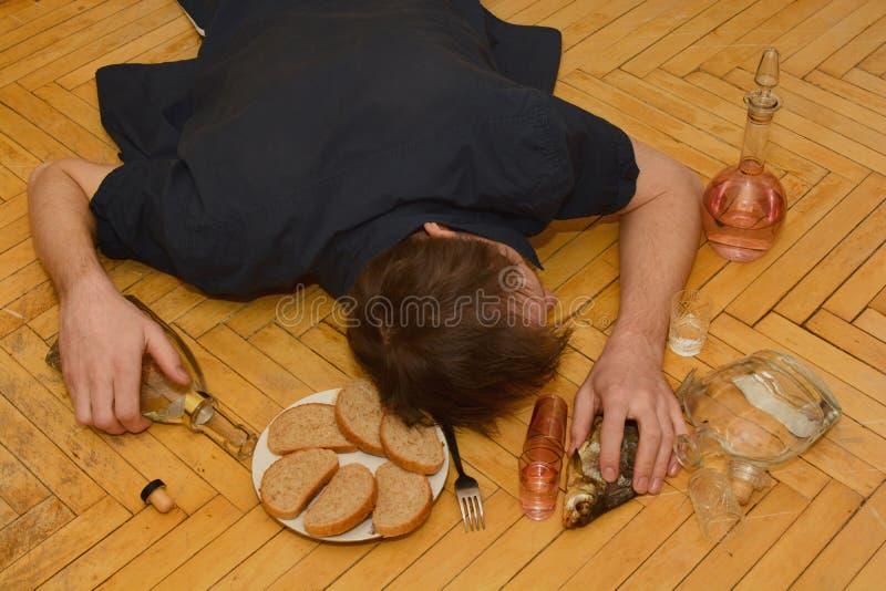 Dronken mens die op de vloer liggen stock foto