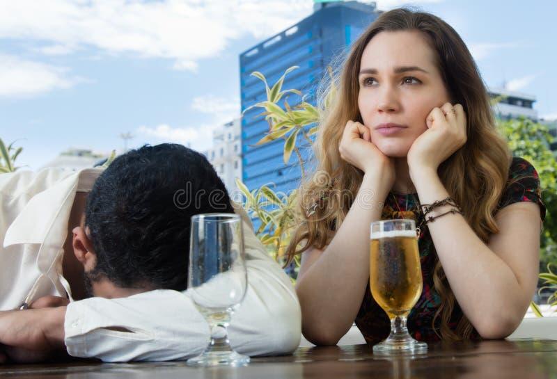 Dronken mens met droevig meisje in een bar stock afbeelding