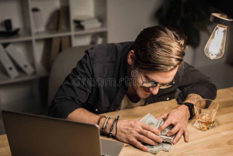 Dronken mens met hoop van contant geld stock afbeeldingen